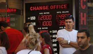 People line up at a currency exchange shop in Istanbul, Tuesday, Aug. 14, 2018.The Turkish lira has nosedived in value in the past week over concerns about Erdogan's economic policies and after the United States slapped sanctions on Turkey angered by the continued detention of an American pastor. (AP Photo/Lefteris Pitarakis)