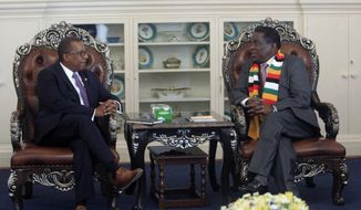 United States Ambassador to Zimbabwe Brian Nichols, left, is seen during a courtesy call with Zimbabwean President elect Emmerson Mnangagwa at his official residence State House in Harare, Wednesday, Aug, 15, 2018. Nichols emphasised the need to respect human rights as Zimbabwe awaits a court ruling on whether the election results are valid. (AP Photo/Tsvangirayi Mukwazhi)