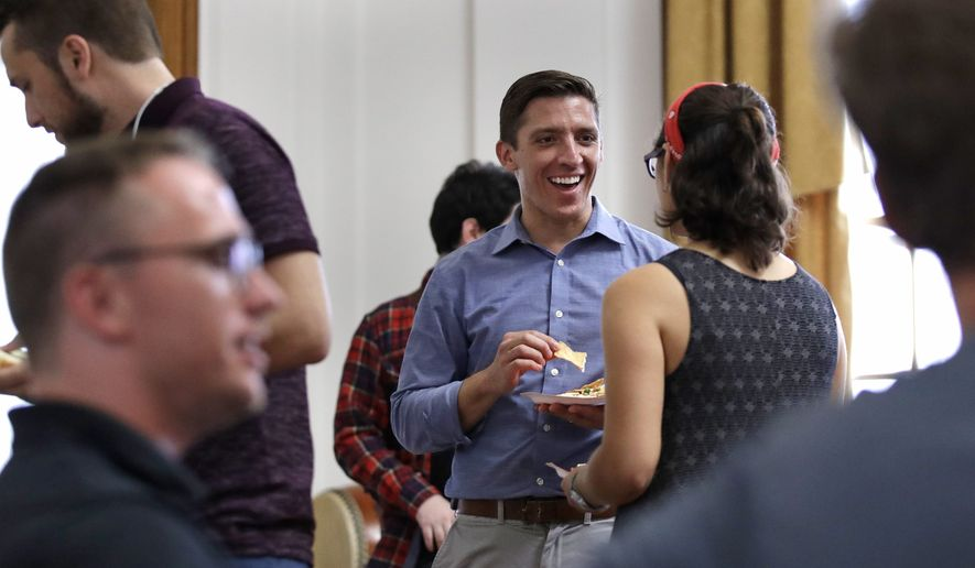 Zak Ringelstein, center, a Democratic candidate for U.S. Senate in Maine, eats a potluck dinner during a gathering prior to a meeting of the Southern Maine Democratic Socialists of America at City Hall in Portland, Maine, Monday, July 16, 2018. On the ground in dozens of states, there is new evidence that democratic socialism is taking hold as a significant force in Democratic politics. (AP Photo/Charles Krupa)