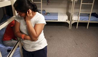 """An unidentified Guatemalan woman is seen inside a dormitory in the Artesia Family Residential Center, a federal detention facility for undocumented immigrant mothers and children in Artesia, N.M, Wednesday, Sept. 10, 2014. The center has been held up by the Obama Administration as visible example of a crackdown on illegal crossings from Central America, while civil rights advocates are suing the federal government, complaining that lack of access to legal representation has turned the Artesia center into a """"deportation mill."""" (AP Photo/Juan Carlos Llorca)"""