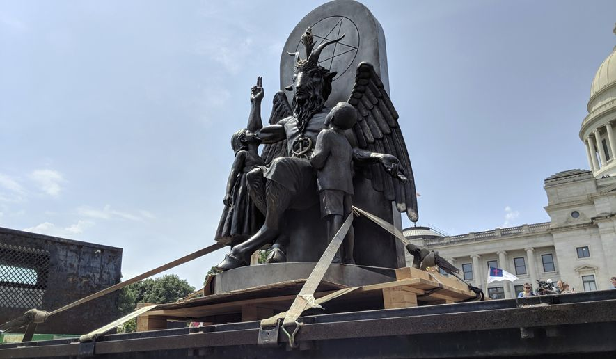 The Satanic Temple unveils its statue of Baphomet, a winged-goat creature, at a rally for the first amendment in Little Rock, Ark., Thursday, Aug. 16, 2018. The Satanic Temple wants to install the statue on Capitol grounds as a symbol for religious freedom after a monument of the Biblical Ten Commandments was installed in 2017. (AP Photo/Hannah Grabenstein)