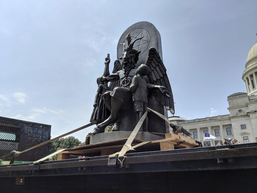 The Satanic Temple unveils its statue of Baphomet, a winged-goat creature, at a rally for the First Amendment in Little Rock, Ark., Thursday, Aug. 16, 2018. The Satanic Temple wants to install the statue on Capitol grounds as a symbol for religious freedom after a monument of the Biblical Ten Commandments was installed in 2017. (AP Photo/Hannah Grabenstein) ** FILE **