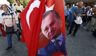 People walk past a street vendor offering for sale Turkish flags and flags of Turkey's President Recep Tayyip Erdogan, at a market in Istanbul, Thursday, Aug. 16, 2018. Beset by a weak currency and tension with the United States, Turkey and Erdogan, is reaching out to Europe in an attempt to shore up relations with major trading partners despite years of testy rhetoric and a stalled bid for EU membership. (AP Photo/Lefteris Pitarakis)