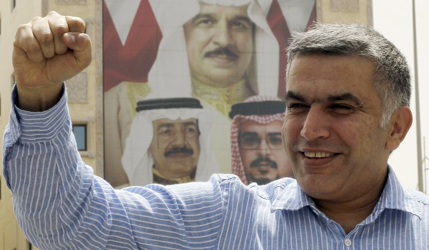 FILE - In this May 28, 2012 file photo, human rights activist Nabeel Rajab gestures as he leaves a police station in Manama, Bahrain.  A United Nations panel said Thursday Aug. 16, 2018, Bahrain should immediately release imprisoned activist Nabeel Rajab. Rajab is serving a five-year prison sentence for tweets he sent in a case widely criticized internationally as the kingdom's government continues a crackdown on dissent. Images on the building at rear shows, clockwise from top, King Hamad bin Isa Al Khalifa, Crown Prince Salman bin Hamad Al Khalifa and Prime Minister Khalifa bin Salman Al Khalifa. (AP Photo/Hasan Jamali, File)