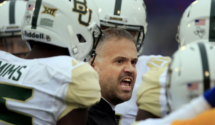 """File-This Nov. 4, 2017, file photo shows Baylor head coach Matt Rhule firing up his team during the first half of an NCAA college football game against Kansas in Lawrence, Kan. Baylor made a lot of progress in Rhule's first season despite that 1-11 record. """"We're tackling issues and tackling character development. We're mentoring, developing, educating and I'm proud of the things we're doing as a college football program,"""" Rhule said.  (AP Photo/Orlin Wagner, File)"""