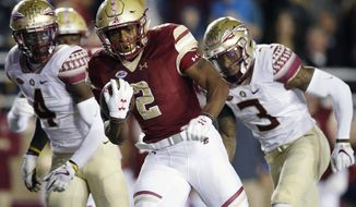 FILE - In this Oct. 27, 2017 file photo, Boston College running back AJ Dillon, center, carries the ball during the first half of an NCAA college football game against Florida State in Boston. With Anthony Brown healthy at quarterback and AJ Dillon coming out of the backfield, Boston College thinks it can get out of the middle of the ACC this year. (AP Photo/Michael Dwyer, File)