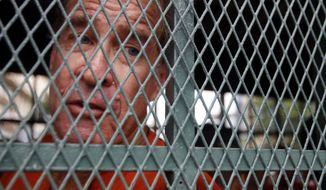 Australian filmmaker James Ricketson sits in a prison truck upon his arrival at Phnom Penh Municipal Court in Phnom Penh, Cambodia, Thursday, Aug. 16, 2018. Ricketson has gone on trial in Cambodia on charges of endangering national security after being arrested last year for flying a drone to capture images of an opposition political rally. (AP Photo/Heng Sinith)