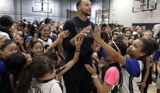 """Golden State Warriors' Stephen Curry, center, greets basketball camp participants after taking a group photo at Ultimate Fieldhouse in Walnut Creek, Calif., Tuesday, Aug. 14, 2018. For the first time, Curry hosted only girls for a free, Warriors-run camp Monday and Tuesday at Walnut Creek's Ultimate Fieldhouse. Last week at the same facility that he has also chosen in recent years, the Golden State star held his Under Armour """"Stephen Curry Select Camp"""" with two of the nation's top high school girls playing mixed right in with the best boys. The two-time MVP and father of two young daughters has made it his mission to better support the girls' game. He asked longtime Warriors camp director Jeff Addiego to plan an all-girls session this summer. (AP Photo/Jeff Chiu)"""