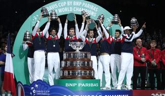 FILE - In this Nov. 26, 2017, file photo, members of the French team lift up their trophies after France won the Davis Cup final at the Pierre Mauroy stadium in Lille, northern France. The Davis Cup will be decided with a season-ending, 18-team tournament beginning next year. The new format replaces the one in which the Davis Cup is played over four weekends throughout the year.  (AP Photo/Christophe Ena, File)
