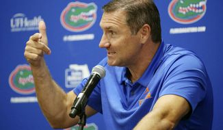 FILE - In this Aug. 2, 2018, file photo, Florida NCAA college football head coach Dan Mullen gestures while speaking at a press conference in Gainesville, Fla. Mullen is tasked with getting Florida to a higher, more acceptable standard _ basically back to where he left the program in 2009.  (Stephen M. Dowell/Orlando Sentinel via AP, File)/