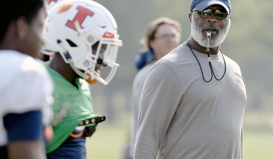 In this Aug. 14, 2018, photo Illinois head football coach Lovie Smith watches his players during training camp at the Campus Rec Fields in Urbana, Ill. A year's worth of experience, intensive strength training and an emerging leader at quarterback could combine to give Illinois a realistic shot at playing some winning football. (Stephen Haas/The News-Gazette via AP)