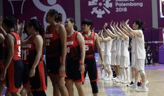 Combined Koreas players, right, wave to their supporters after defeating Indonesia in their women's basketball match at the 18th Asian Games in Jakarta, Indonesia, Wednesday, Aug. 15, 2018. (AP Photo/Tatan Syuflana)