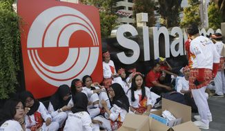 In this Aug. 5, 2018, photo, students sit in front of building that houses the headquarters of Sinarmas Group, one of Indonesia's largest palm oil company, in Jakarta, Indonesia. The main global group for certifying sustainable wood has suspended plans to give its influential endorsement to Indonesian paper giant Sinarmas after revelations it cut down tropical forests and used an opaque corporate structure to hide its activities. (AP Photo/Tatan Syuflana)