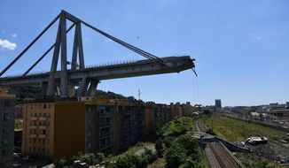 A view of the evacuated houses built under the remains part of the collapsed Morandi highway bridge, in Genoa, northern Italy, Wednesday, Aug. 15, 2018. A bridge on a main highway linking Italy with France collapsed in the Italian port city of Genoa during a sudden, violent storm, sending vehicles plunging 90 meters (nearly 300 feet) into a heap of rubble below. (AP Photo/Nicola Marfisi)