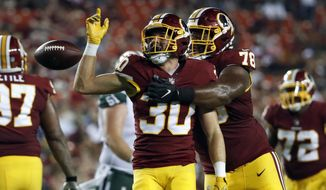 Washington Redskins defensive back Troy Apke (30) celebrates his interception with defensive tackle Ondre Pipkins (78) during the first half of a preseason NFL football game against the New York Jets, Thursday, Aug. 16, 2018, in Landover, Md. (AP Photo/Alex Brandon)