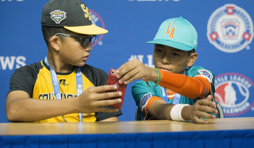 In this photo provided by Georgianna DeCarmine, Georgia shortstop Tai Peete, left, uses Google Translate on his phone to communicate with Panama outfielder Rolando Rodriguez during an interview at the Little League World Series in South Williamsport, Pa., Tuesday, Aug. 14, 2018. (Georgianna DeCarmine via AP)