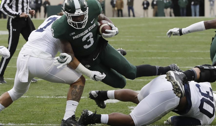 File- This Nov. 4, 2017, file photo shows Michigan State running back LJ Scott (3) being  tackled by Penn State linebacker Koa Farmer, left, during the first half of an NCAA college football game in East Lansing, Mich. Scott enters his senior season with some impressive career rushing stats: 2,591 yards and 25 touchdowns. A good final season could put him in the top four on the school's career list in both categories but he also has room for improvement. He was part of a team-wide fumbling problem that plagued the Spartans last year.(AP Photo/Carlos Osorio, File)