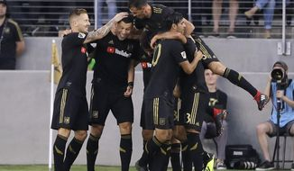 Los Angeles FC's Christian Ramirez, second from left, is mobbed by teammates after scoring against Real Salt Lake during the first half of an MLS soccer match Wednesday, Aug. 15, 2018, in Los Angeles. (AP Photo/Marcio Jose Sanchez)