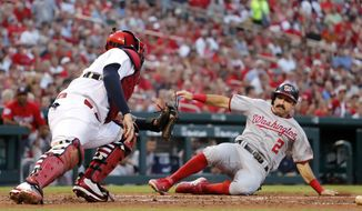 Washington Nationals' Adam Eaton (2) scores past St. Louis Cardinals catcher Yadier Molina during the fourth inning of a baseball game Thursday, Aug. 16, 2018, in St. Louis. (AP Photo/Jeff Roberson)