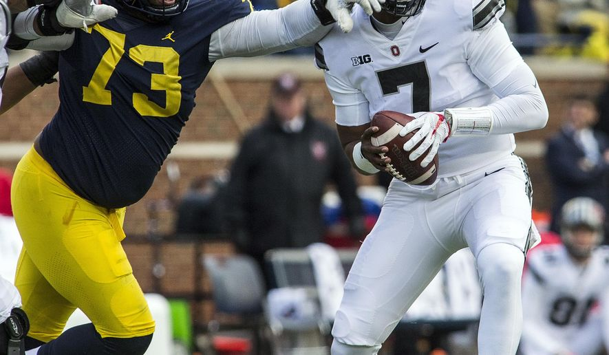 File-This Nov. 25, 2017, file photo shows Michigan defensive lineman Maurice Hurst (73) reaching for Ohio State quarterback Dwayne Haskins (7) during the third quarter of an NCAA college football game in Ann Arbor, Mich.  The major obstacle to Haskins becoming Ohio State's next starting quarterback was erased when Joe Burrow decided to transfer to LSU after spring practice rather than battle it out with Haskins in fall camp. Haskins already secured his place in Buckeyes lore by winning last year's Michigan game, takes the keys from four-year starter J.T. Barrett. (AP Photo/Tony Ding, File)