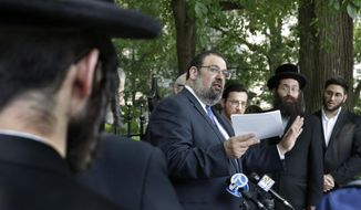 Attorney Avi Schick, center, of Parents for Educational and Religious Liberty in Schools, speaks during a news conference outside City Hall, in New York, Thursday, Aug. 16, 2018. New York City education officials say leaders at 15 ultra-Orthodox Jewish schools that were among the subjects of a 2015 complaint have expressed a commitment to expanding students' exposure to secular education. (AP Photo/Richard Drew)