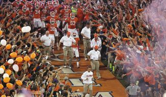FILE - In this Oct. 19, 2013, file photo, Clemson head coach Dabo Swinney leads the team down the lane before the first half of an NCAA college football game against the Florida State, in Clemson, S.C. (AP Photo/Mike Stewart, File)