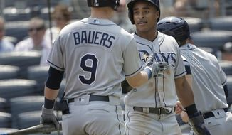 Tampa Bay Rays' Mallex Smith, right, is greeted by Jake Bauers (9) after scoring a run during the first inning of a baseball game against the New York Yankees at Yankee Stadium Thursday, Aug. 16, 2018, in New York. (AP Photo/Seth Wenig)