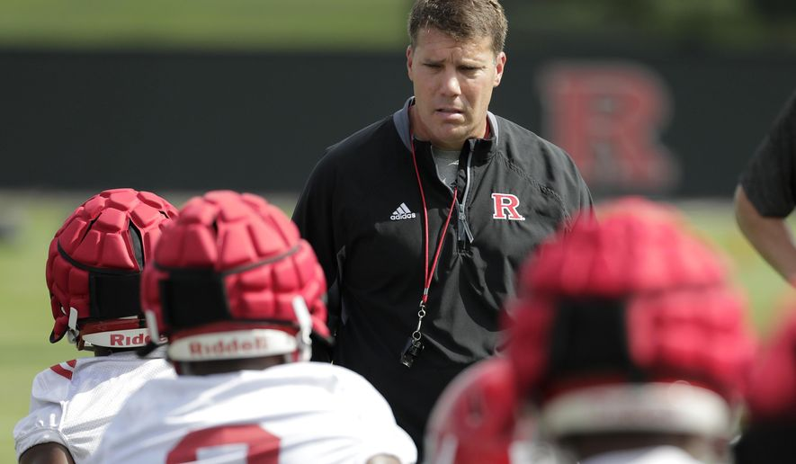 In a photo taken Friday, Aug. 3, 2018, Rutgers head coach Chris Ash, center, talks to running backs as they stretch during NCAA college football training camp in Piscataway, N.J. (AP Photo/Julio Cortez)