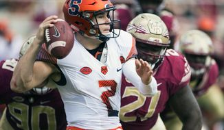 FILE - In this Nov. 4, 2017, file photo, Syracuse quarterback Eric Dungey throws the ball away as Florida State defensive tackles Demarcus Christmas (90) and Marvin Wilson close in during the first half of an NCAA college football game in Tallahassee, Fla. (AP Photo/Mark Wallheiser, File)