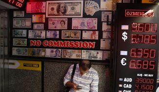 A man uses his mobile as he sits in a currency exchange shop in Istanbul, Thursday, Aug. 16, 2018. Beset by a weak currency and tension with the United States, Turkey is reaching out to Europe in an attempt to shore up relations with major trading partners despite years of testy rhetoric and a stalled bid for EU membership. The overtures by Turkish President Recep Tayyip Erdogan, who has harshly criticized Germany and other European nations in the past, are part of a diplomatic campaign to capitalize on international unease over U.S. President Donald Trump and American tariff disputes. (AP Photo/Lefteris Pitarakis)