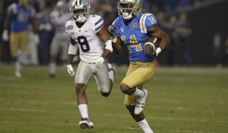 FILE - In this Dec. 26, 2017, file photo, UCLA wide receiver Theo Howard (14) runs away from Kansas State defensive back Duke Shelley for a touchdown during the Cactus Bowl NCAA college football game in Phoenix. Howard is among several returning Bruins veterans who hope to return the program to Pac-12 title contention in their first year under new coach Chip Kelly. (AP Photo/Rick Scuteri, File)