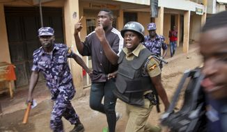 A supporter of pop star Kyagulanyi Ssentamu is detained following a demonstration in the Kamwokya area of Kampala, Uganda, Thursday, Aug. 16, 2018.  Supporters were demonstrating in support of pop singer and prominent critic of Uganda's government Kyagulanyi Ssentamu, whose stage name is Bobi Wine, who was charged with unlawful possession of firearms and ammunition in a military court on Thursday for his alleged role in clashes in which the longtime president's motorcade was attacked by people throwing stones.(AP Photo/Stephen Wandera)