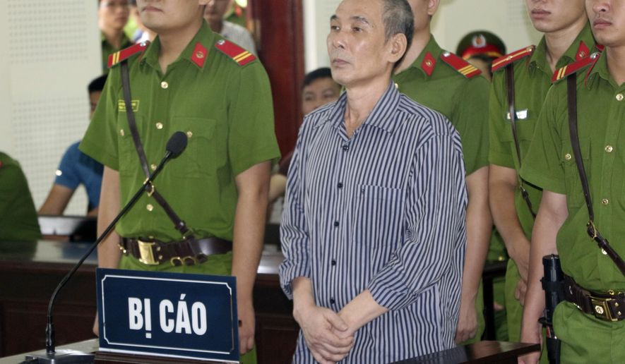 Activist Le Dinh Luong, center, stands trial in central province of Nghe An, Vietnam, Thursday, Aug. 16, 2018. Luong was sentenced to 20 years in prison after the court found him guilty of attempting to overthrow the government at the one-day trial. It was one of the toughest sentences in years for national security crimes. International human rights groups have called for his release. (Bich Hue/Vietnam News Agency)