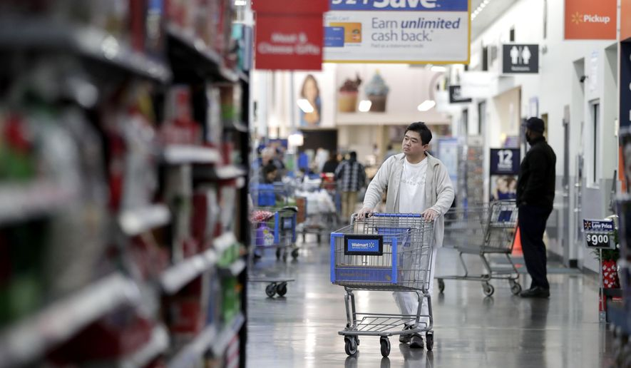 FILE- In this Nov. 9, 2017, file photo, a man pushes a cart while shopping at a Walmart store in North Bergen, N.J. Walmart Inc. reports earnings on Thursday, Aug. 16, 2018. (AP Photo/Julio Cortez, File)
