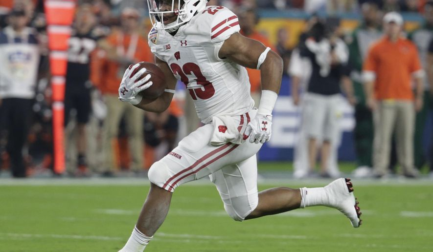 FILE - In this Dec. 30, 2017, file photo, Wisconsin running back Jonathan Taylor (23) runs the ball during the first half of the Orange Bowl NCAA college football game against Miami, in Miami Gardens, Fla. Running back Jonathan Taylor probably wouldn't be drawing hype as a Heisman Trophy candidate if not for the holes opened by the Badgers' offensive line during his record-setting freshman season. The line is tough, physical and agile in typical Wisconsin fashion, and all five starters are back.(AP Photo/Lynne Sladky, File)