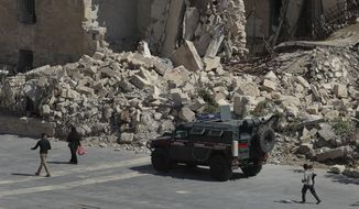 In this photo taken on Thursday, Aug. 16, 2018, Syrians pass by a Russian military police vehicle with destroyed buildings in the background in the city of Aleppo, Syria. Russian air defense assets in Syria claim to have downed 45 drones targeting their main base in the country, its military said Thursday, after an attack by the Islamic State group on a Syrian army base a day earlier killed seven troops. (AP Photo/Sergei Grits)
