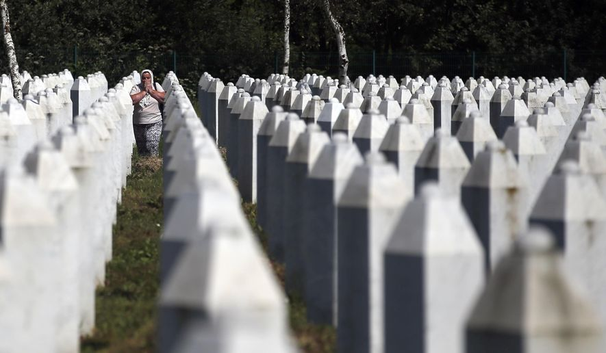 A Bosnian Muslim woman reacts as she walks among gravestones at the memorial centre of Potocari near Srebrenica, 150 kms north east of Sarajevo, Bosnia, Tuesday, Aug. 14, 2018. The leader of Bosnia's Serbs has downplayed the massacre of some 8,000 Bosnian Muslims in Srebrenica during the war in 1995 and called for the reopening of an investigation into the worst carnage in Europe since World War II. (AP Photo/Darko Vojinovic)