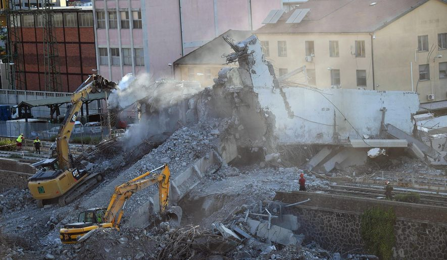 Firefighters remove debris of the collapsed Morandi highway bridge in Genoa, Italy, Thursday, Aug. 16, 2018. (Luca Zennaro/ANSA via AP)