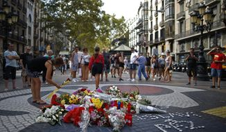 A woman places a flower around a memorial tribute of flowers, messages and candles on Barcelona's historic Las Ramblas in Barcelona, Thursday, Aug. 16, 2018, the day before to the anniversary of the attacks that took place here on Aug. 17, 2017 killing 16 people and injuring more than 120. (AP Photo/Manu Fernandez)
