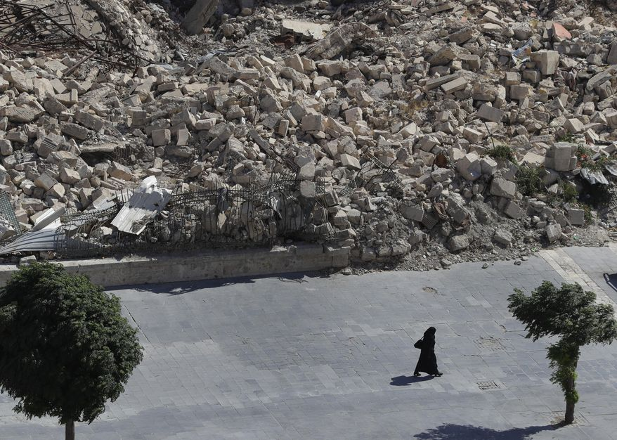In this photo taken on Thursday, Aug. 16, 2018, a woman walks past the remnants of destroyed buildings in the city of Aleppo, Syria. Russian air defense assets in Syria claim to have downed 45 drones targeting their main base in the country, its military said Thursday, after an attack by the Islamic State group on a Syrian army base a day earlier killed seven troops. (AP Photo/Sergei Grits)