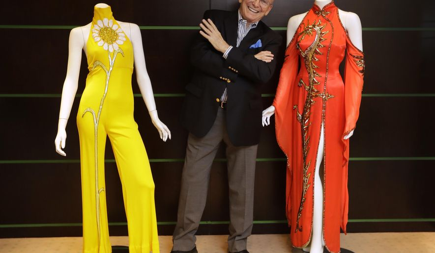 Fashion and Costume Designer Bob Mackie poses with two of his iconic designs, a scarlet red satin gown worn by Cher in 1975, right, and a marigold jersey jumpsuit worn by Cher between 1971-1976, left, in London, Thursday, Aug. 16, 2018. The gowns are estimated at 3,000-5,000 US Dollars ( 2,363-3,938 UK Pounds) each will be auctioned in the 'Property from the Collection of Bob Mackie' sale by Julien's Auctions in Los Angeles on Nov. 17. (AP Photo/Kirsty Wigglesworth)