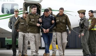 Police officers escort Franco Sepulveda off a plane, after he was detained in Antofagasta, for making multiple bomb threats about several airline flights, in Santiago, Chile, Friday, Aug. 17, 2018. Sepulveda caused nine commercial airline flights to take emergency measures. Police chief Mario Rojas said Sepulveda was angry because his suitcase was not returned. (Javier Torres/Aton Chile via AP)