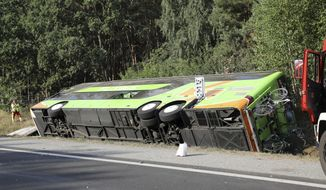 A bus sits beside the Autobahn A 19 in Linstow near Rostock, northern Germany, Friday, Aug. 17, 2018, after it was driven into a ditch and turned over. Six people were seriously injured and a further 10 slightly hurt. (Bernd Wuestneck/dpa via AP)