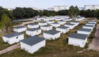 In this Aug. 16, 2018 photo houses originally built for refugees sit on the site of a former refugee center in Hamburg, Germany. The boxy houses, 28 square meters (301 square feet) in size, were offered this week as potential guest houses, workshops, or sport or yoga venues. The minimum offer price was 1,000 euros (US$1,130), but there were two catches: buyers needed to have building permission to put the houses up and pick them up themselves. (Daniel Bockwoldt/dpa via AP)