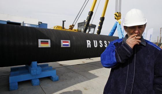 FILE - In this Friday, April 9, 2010 file photo a Russian construction worker smokes in Portovaya Bay some 170 kms (106 miles) north-west from St. Petersburg, Russia, during a ceremony marking the start of Nord Stream pipeline construction. Merkel and Putin will meet on Saturday in the German government's guesthouse Meseberg, north of Berlin, Saturday, Aug. 18, 2018. The topics will include the civil war in Syria, the conflict in Ukraine, and energy questions. (AP Photo/Dmitry Lovetsky, file)