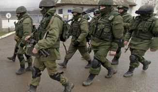In this March 20, 2014 photo, Pro-Russian soldiers march outside an Ukrainian military base in Perevalne, Crimea. (Associated Press) **FILE**