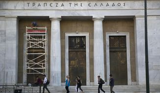 FILE - In this file photo dated Friday, June 22, 2018, people walk past the Bank of Greece headquarters as workers repair the facade of the building in central Athens.  Greece officially emerges from its bailout program on upcoming Monday, Aug. 20, 2018, after eight years of cutbacks enforced in return for three massive loan infusions, but the huge debt pile in Greece and throughout Europe could take generations to defuse.  (AP Photo/Petros Giannakouris, FILE)