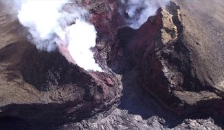 """In this Aug. 11, 2018 aerial photo provided by the United States Geological Survey shows diminished volcanic activity on Kilauea's lower East Rift Zone. Slowing activity at Hawaii's Kilauea volcano is prompting scientists to downgrade their alert level for the mountain. The U.S. Geological Survey said Friday, Aug. 17, it issued a """"watch"""" for Kilauea's ground hazards; that's down from a """"warning."""" Geologists say lava mostly stopped flowing on Aug. 6. (USGS via AP)"""