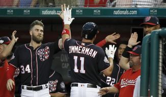 Washington Nationals' Ryan Zimmerman celebrates his solo home run with Bryce Harper (34) and others during the second inning of a baseball game against the Miami Marlins at Nationals Park, Friday, Aug. 17, 2018, in Washington. (AP Photo/Alex Brandon)
