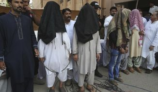 FILE - In this Aug. 10, 2018, file photo, family members of suicide bomber Hafeez Nawaz, with their faces covered, are presented before media for in Karachi, Pakistan. Nawaz killed 149 people and wounding 300 others. At age 20, Hafeez Nawaz left his religious school in Karachi to join the Islamic State group in Afghanistan. Three years later he was back in Pakistan to carry out a deadly mission. (AP Photo/Fareed Khan, File)